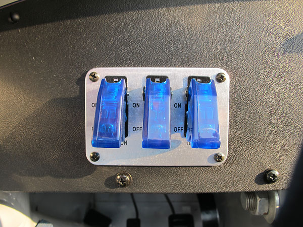Three toggle switches, under plastic covers to prevent accidentally turning them on.