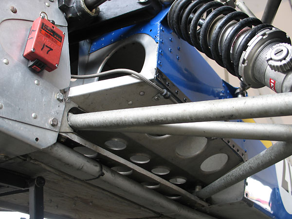 Aluminum coolant piping is routed below the lower-front suspension pickups (and also the fuel tanks).