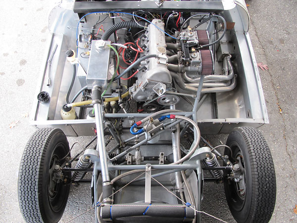 Rearward halves of Elva MkIV two-piece upper control arms are anchored to rubber frame mounts.