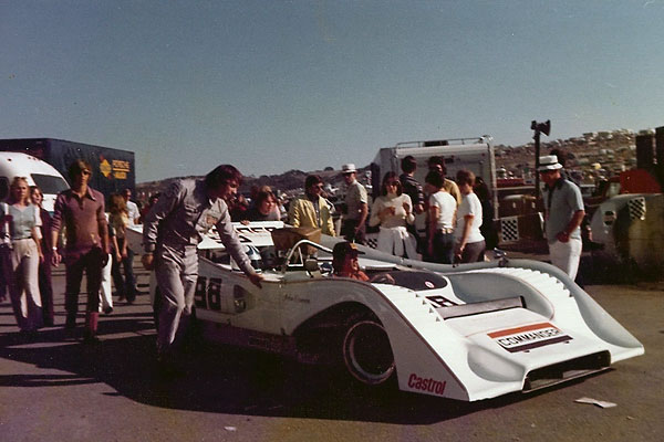 John Cannon helps push his McLaren M8F through the paddock at Laguna Seca.