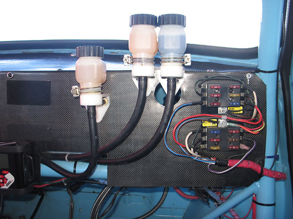 Remote brake and clutch master cylinder reservoirs. Buss six-fuse terminal blocks.